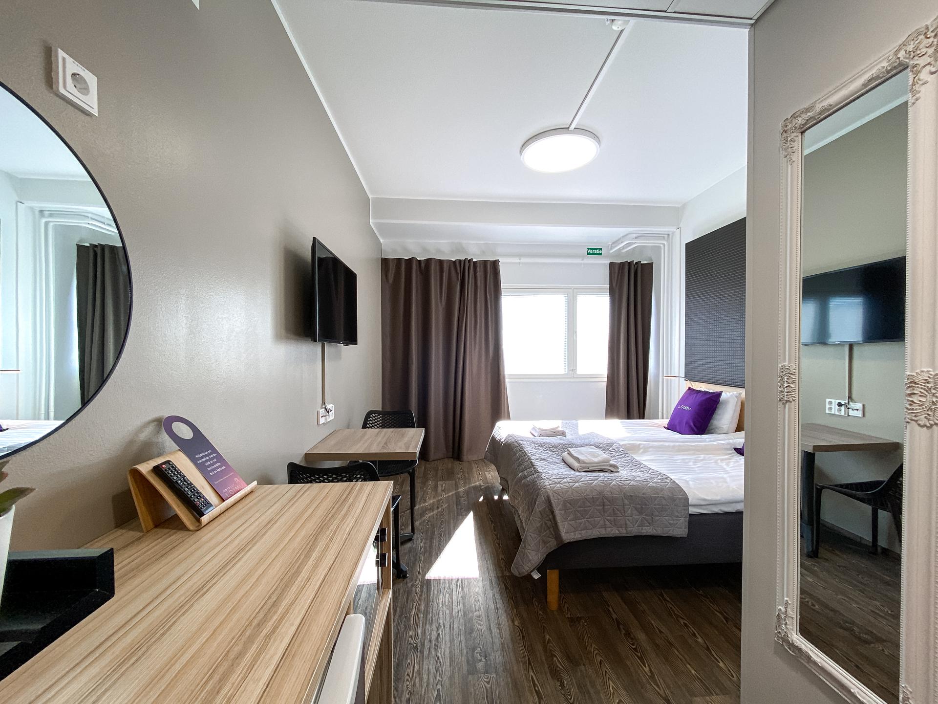 Kaksi hotellin sänkyä ja koivutapetti